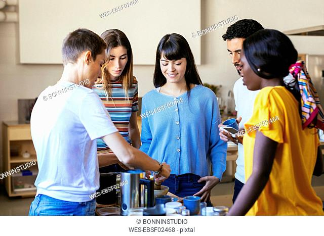 Friends and instructor in a cooking workshop preparing a drink