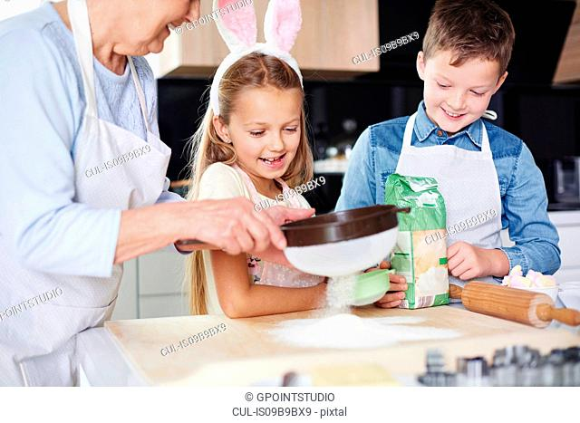 Girl and brother watching grandmother sift flour for easter bake at kitchen counter
