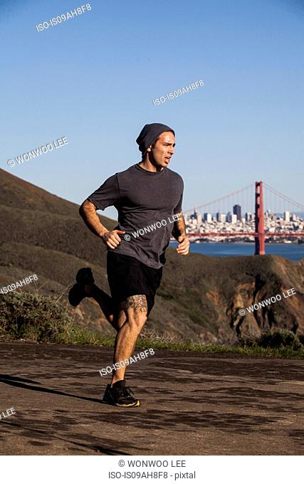 Young man out running with golden gate bridge in background