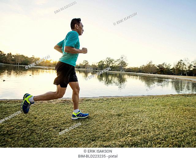 Older Chinese man running in park
