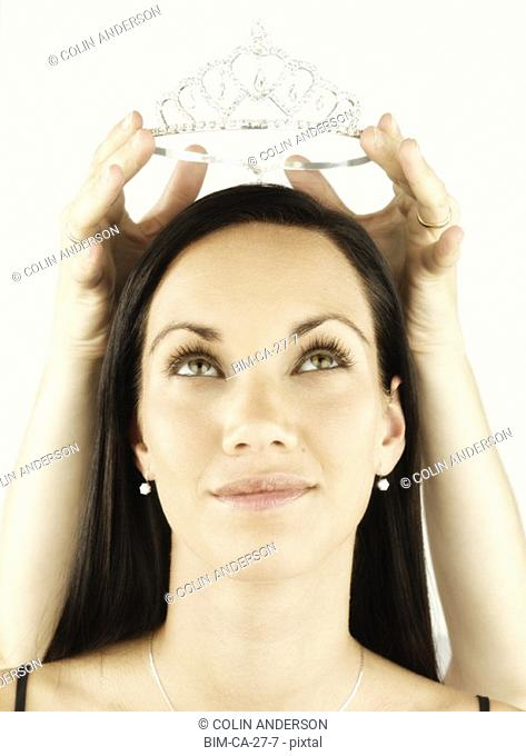 Woman having tiara placed on her head