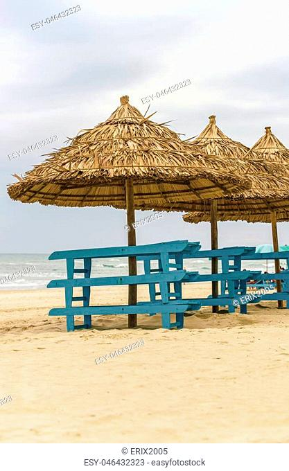 Sunbeds and Palm shelters at the China Beach in Da Nang, Vietnam. It is also called Non Nuoc Beach. South China Sea on the background