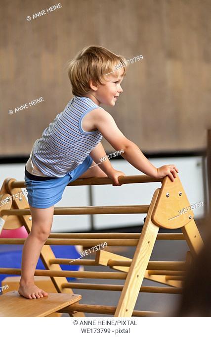 2 year old boy climbing a ladder in a gym. Germany