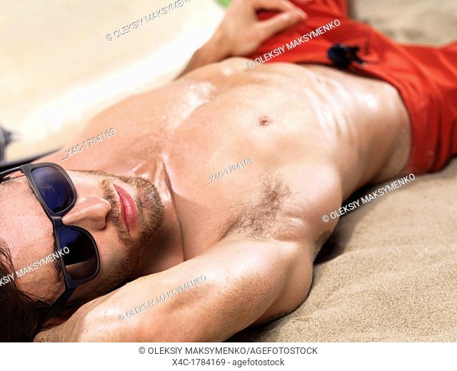 Sexy young man with wet bare torso lying on sand at the beach