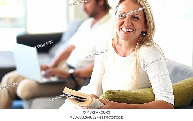 Mature woman reading on the sofa at home while her husband sits working in the background