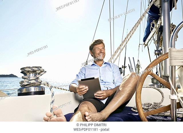Portrait of happy mature man with tablet sitting on deck of his sailing boat