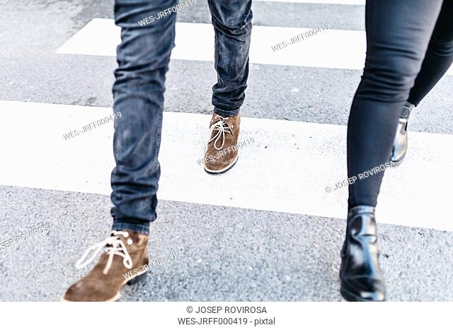 Legs of man and woman walking on crosswalk