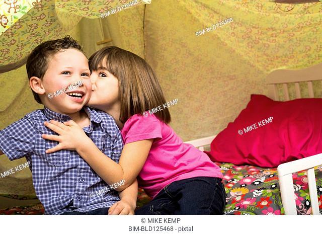 Caucasian children kissing in blanket fort