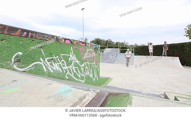 Teenager with city scooter in Skate park, Leioa, Bizkaia, Basque Country, Spain