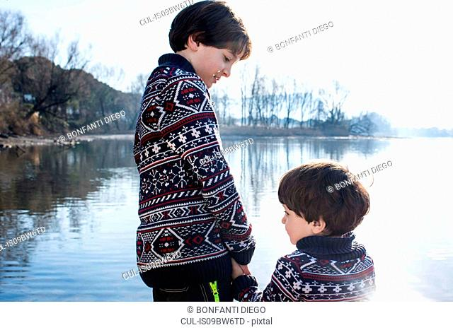 Boy and toddler brother in matching sweaters holding hands on lakeside, Lake Como, Lecco, Lombardy, Italy
