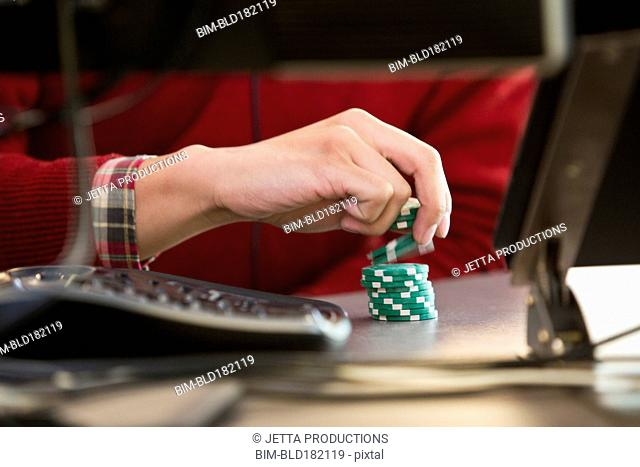 Vietnamese businessman with poker chips at office desk