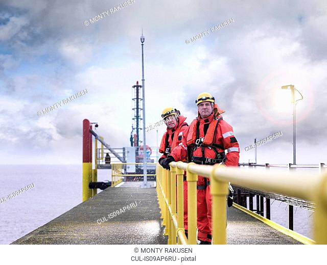 Offshore windfarm workers on jetty at sea, portrait