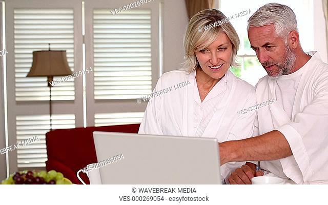 Happy couple using laptop together in bathrobes