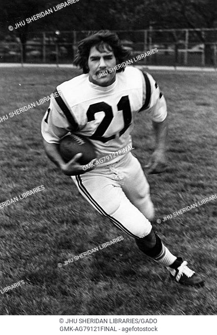 Johns Hopkins University football player in uniform carrying the football in motion on a field at Johns Hopkins University, Baltimore, Maryland, 1975