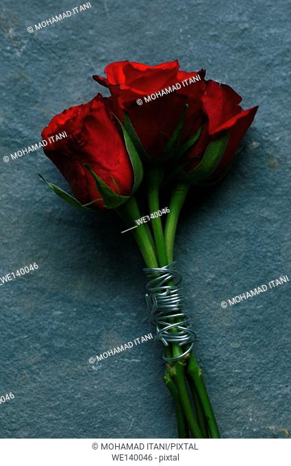 Three red roses tied up with metal wire
