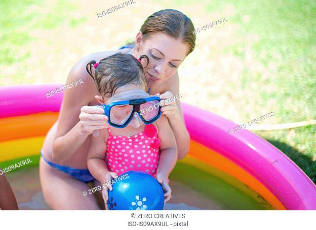 Mother putting goggles on daughter in inflatable pool