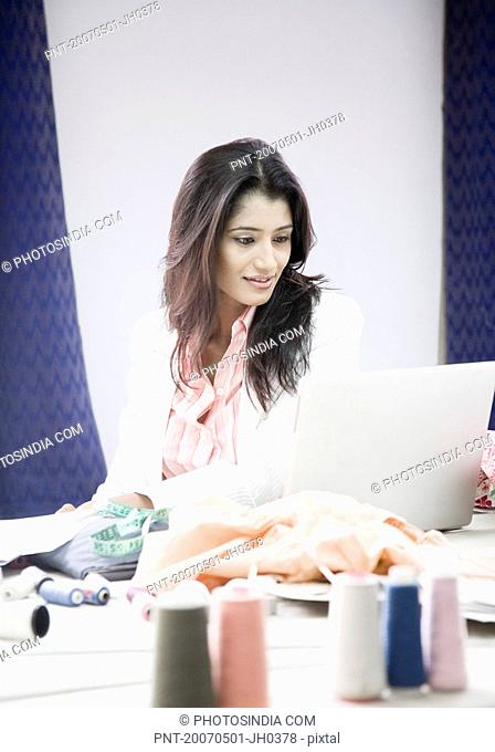 Female fashion designer sitting in front of a laptop