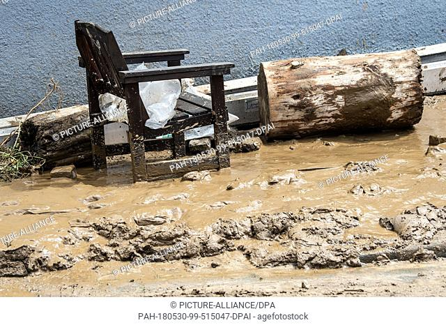 30 May 2018, Germany, Bad Gandersheim: A wooden chair standing in the mud in a courtyard entrance. The floods which occured after heavy rain on Tuesday evening...