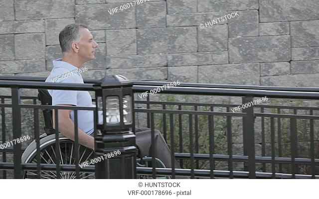 Man with spinal cord injury in a wheelchair using accessible wheelchair ramp and turning around