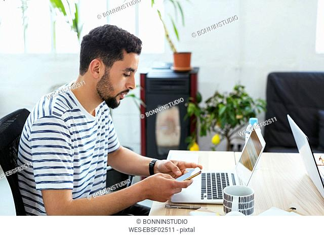 Young man using laptop and cell phone at desk in office