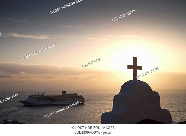View of church and sea ferry at sunset, Oia, Santorini, Cyclades, Greece