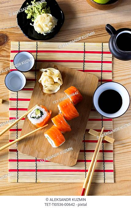 Salmon sushi on cutting board with condiments