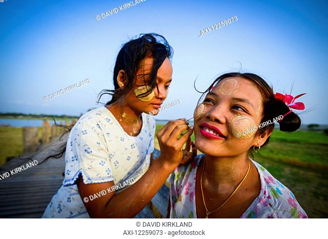 A young woman receives traditional face paint on U Bein Bridge; Mandalay, Myanmar