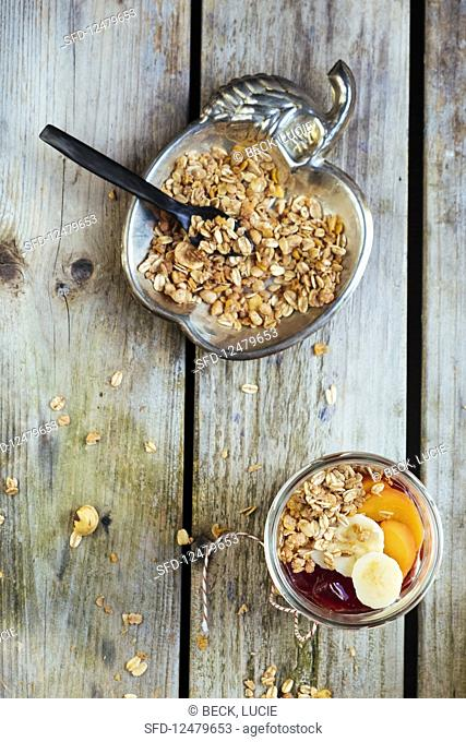 Yoghurt, jam, fruit and granola and oatmeal flakes