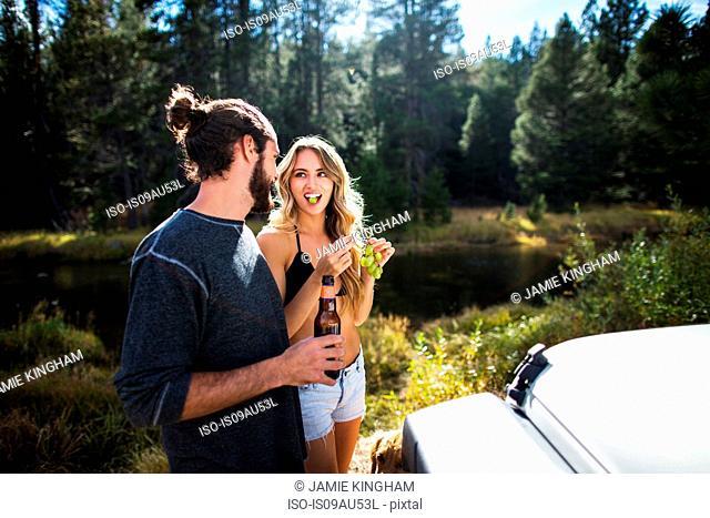 Young couple eating grapes on riverside, Lake Tahoe, Nevada, USA
