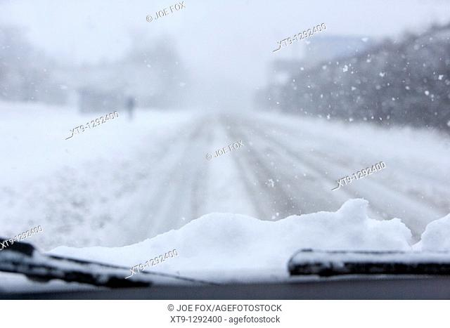car with snow on the bonnet driving along a cold frozen road on a cold snowy winters day Belfast Northern Ireland