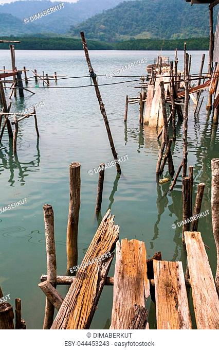 Broken pier of wooden planks in the Thai fishing village