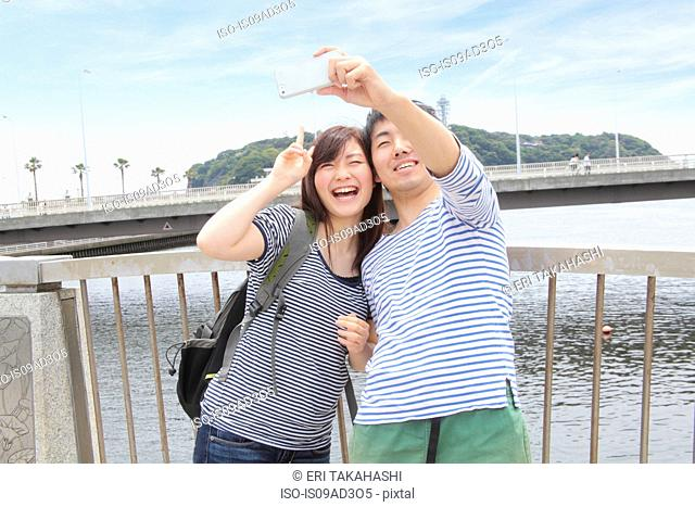 Young couple taking self portrait photograph with smartphone