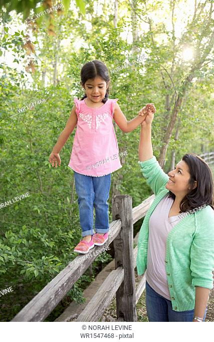 A young girl in a pink shirt and jeans, walking along a fence holding her mother's hand