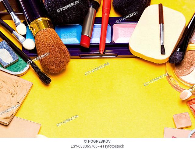 Different makeup cosmetics and accessories laid out as semicircular frame. Bright yellow background. Copy space