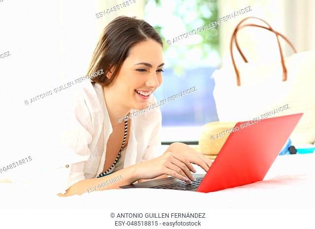 Happy hotel guest using a laptop in a room on summer holidays on the beach