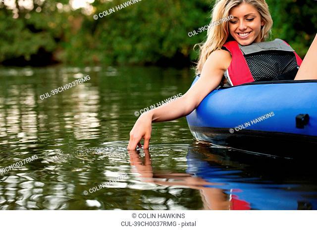 Woman dangling hand in still creek
