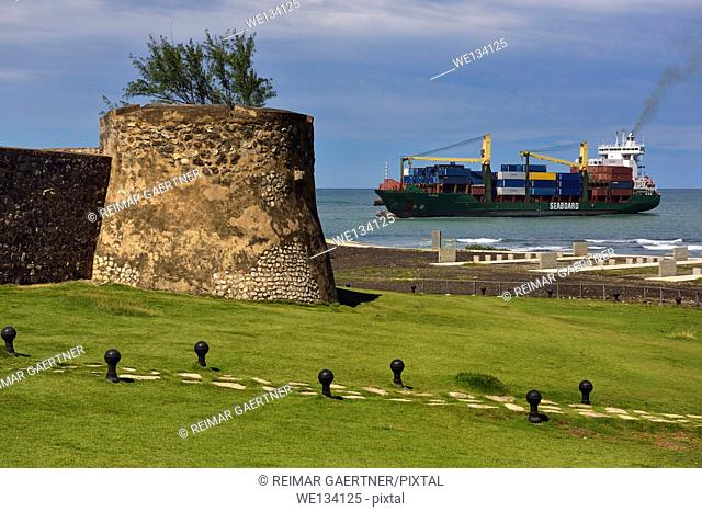 Container ship entering Puerto Plata Bay and port with walls of San Felipe fortress