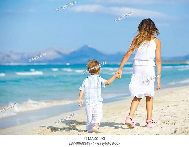 Back view of young beautiful girl and her brather walking at pretty beach. Majorca, Spaine