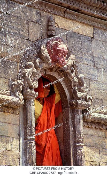 Nepal: A woman sheletering in a shrine at Pashupatinath, Kathmandu