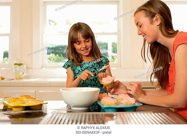 Young girl with older sister icing cupcakes