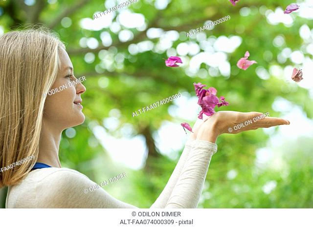 Young woman catching falling petals, side view