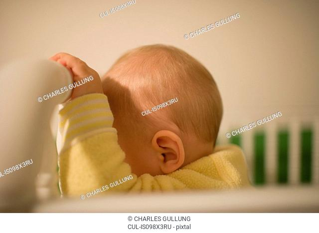 Toddler boy resting forehead on cot