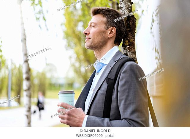 Relaxed businessman with takeaway coffee in a park