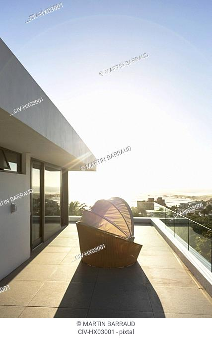 Covered patio chair on sunny modern luxury balcony under blue sky