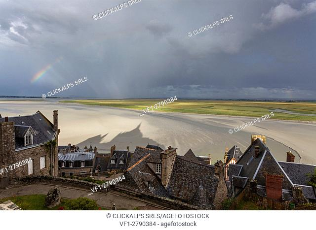 Mont Saint Michel, Normandy, France. A view of bay with rainbow and abbey's shadow