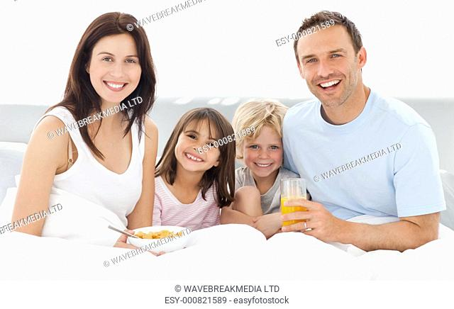 Cheerful family having breakfast together on the bed at home