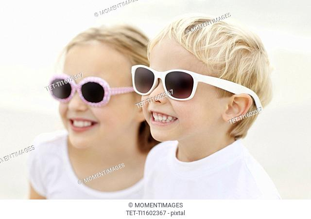 Girl 10-11 and boy 4-5 wearing sunglasses on beach