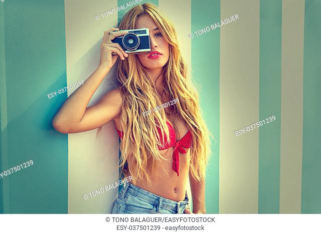 Blond teen summer girl with vintage photo camera in blue stripes wall background filtered image