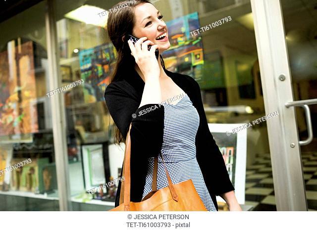 Puerto Rico, San Juan, Woman walking on street and talking on mobile phone
