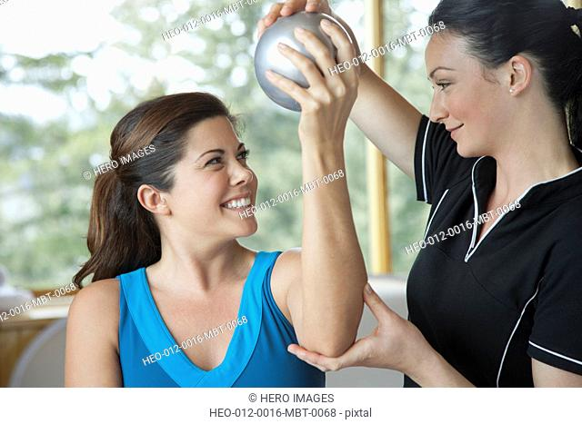 physical therapist guiding mid-adult woman